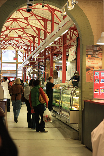 Customers ordering from a butcher at one of the indoor stalls.