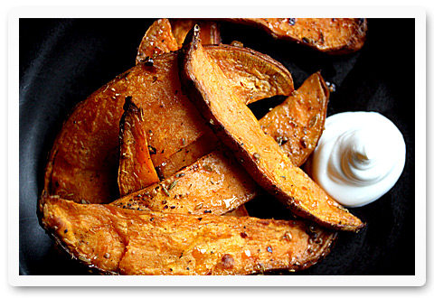 Savory sweet potato fries on a plate with a dollop of sour cream